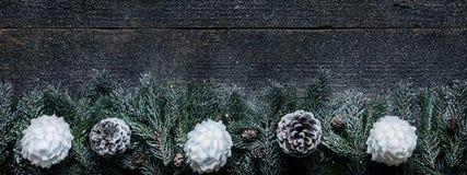 Śnieżny Bożenarodzeniowy tło, Jedlinowe gałąź Z Sosnowymi rożkami I Xmas Baubles Na Drewnianym tle, zdjęcia stock