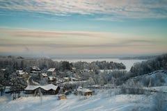 Śnieżny las, chałupy i lukrowy jezioro przy zmierzchem Zdjęcia Royalty Free