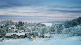 Śnieżny las, chałupy i lukrowy jezioro przy zmierzchem Zdjęcie Royalty Free