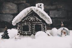 Śnieżny Piernikowy dom z płatkami śniegu choinka i kula ziemska na kamiennej ściany tle Święta ciasteczka domowej roboty Zdjęcie Stock