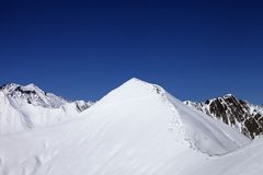 Śnieżny piste skłon i błękita jasny niebo przy ładnym zima dniem Zdjęcie Royalty Free
