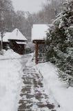 Śnieżyści domy w zima parku, rozjaśniającym ścieżka płytki i dryfy fotografia royalty free