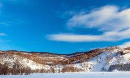 Śnieżyści wzgórza i niebieskie niebo na Kamchatka Zdjęcia Royalty Free