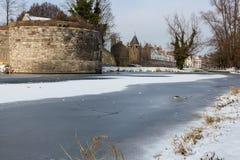 Śnieg na zamarzniętym stawie z średniowieczną ścianą w tle obraz royalty free