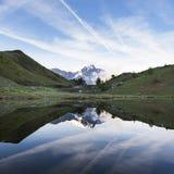 Śnieg nakrywająca góra odbijał w wodzie mały jezioro blisko col De Vars w francuskich alps fotografia royalty free