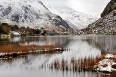 Śnieg odkurzać Glyder góry wzrasta w chmury odbijali w Llyn Ogwen Fotografia Stock