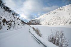 Śnieg zakrywał drogowego bieg wzdłuż lodowatego fjord Fotografia Royalty Free