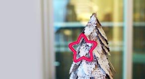 Śnieg zakrywał drzewa z sezonowym czerwieni gwiazdy ciastka krajaczem Zdjęcia Royalty Free