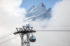 Śnieg zakrywał halnych szczyty i wagony kolei linowej w Grindelwald, Szwajcaria Zdjęcia Royalty Free