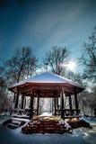 Śnieg zakrywał kioska w parku z niebieskim niebem Fotografia Stock