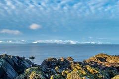 Śnieg Zakrywający Arran i liszaj Zakrywać skały na Portencross Foreshore obraz royalty free