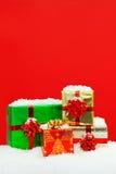 Śnieg zakrywający Bożenarodzeniowych teraźniejszość czerwieni tło. Zdjęcie Stock
