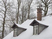 Śnieg zakrywający dach z ceglanym kominu i zatoki łęku okno z ici zdjęcia royalty free
