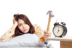 Śpiąca Azjatycka dziewczyna budził się szlagierowego budzika z młotem obraz stock