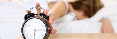 Śpiąca młoda kobieta próbuje zwłoka budzika obrazy stock