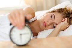Śpiąca młoda kobieta próbuje zwłoka budzika Fotografia Royalty Free