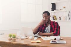 Śpiący czarny biznesmen w przypadkowym biurze, praca z laptopem Zdjęcia Royalty Free