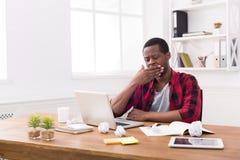 Śpiący czarny biznesmen w przypadkowym biurze, praca z laptopem Zdjęcie Royalty Free