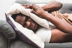 Śpiący facet budzi się wcześnie i no chce wstawać po tym jak słuchający budzika sygnał zdjęcie royalty free