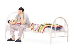 Śpiący facet patrzeje budzika obrazy stock
