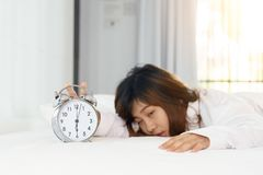 Śpiący kobiety próbować obraca daleko budzika w ranku zdjęcie stock