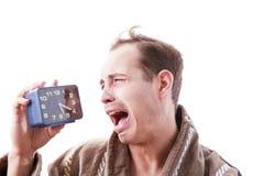 Śpiący mężczyzna płacz z budzikiem w ręce w wczesnym poranku Fotografia Stock
