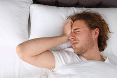 Śpiący młodego człowieka lying on the beach na poduszce bedtime obraz stock