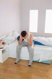 Śpiący przypadkowy mężczyzna obsiadanie na łóżku Zdjęcie Royalty Free