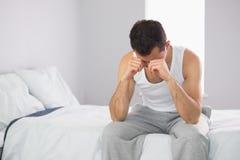 Śpiący przypadkowy mężczyzna obsiadanie na łóżku naciera jego ono przygląda się Obrazy Royalty Free