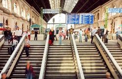 Śpieszyć się ludzi wśrodku struktury Keleti stacja kolejowa z pociągami na platformie Fotografia Royalty Free