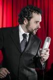 Śpiewacki mężczyzna z czarnym mikrofonem na tle i kostiumem Obrazy Royalty Free