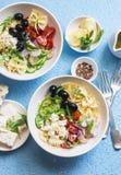 Śródziemnomorska makaron sałatka Makaronu farfalle, pomidory, ogórki, oliwki, feta ser i arugula sałatka, Na błękitnym tle, wierz Obraz Royalty Free