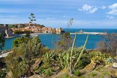 Śródziemnomorska roślinność z morzem i wioską Obrazy Royalty Free