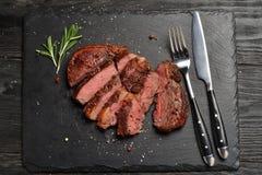 Średni Ribeye stek na czerń kamienia talerzu Obrazy Stock