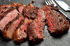 Średni Rzadki Ribeye stek na czerń kamienia talerzu fotografia stock