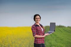 Średniorolna dziewczyna z laptopem w rapeseed obraz stock