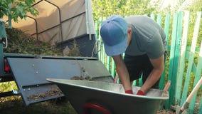 Średniorolna pracownika ładunku trawa i grat w styl życia przyczepy ciężarówkę od wheelbarrow z pitchforks i rękami cz?owieku zdjęcie wideo