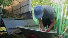Średniorolna pracownika ładunku trawa i grat w styl życia przyczepy ciężarówka od wheelbarrow z pitchforks i rękami cz?owieku zdjęcie wideo