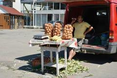 Średniorolnego sprzedawania uprawy z bagażnika jego samochód Obrazy Stock