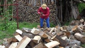 Średniorolny facet przygotowywa organicznie drewna paliwo blisko woodshed dla zima sezonu 4K zbiory wideo
