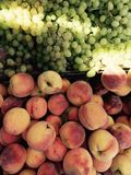 Średniorolny ` s rynek jest zalany w świetle słonecznym, organicznie brzoskwinie i winogrona i zdjęcia royalty free
