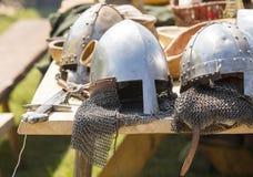 Średniowieczny opancerzenie, hełmy kłama na drewniany stołowy plenerowym Obrazy Royalty Free