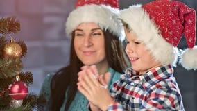 Środek w górę szczęśliwej rodzinnej uśmiechniętej matki i ślicznego dziecko syna dekoruje choinki wpólnie zbiory