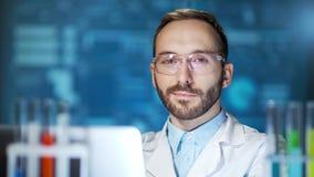 Środek w górę uśmiechniętego męskiego naukowa jest ubranym szkła i bielu żakiet używać laptop w lab zdjęcie wideo