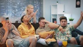 Środek zamknięty w górę mieszanych biegowych ludzi czuć smutny i zaakcentowany zapałczany nie udać się ogląda na TV zbiory wideo