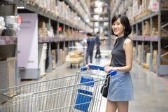 ?rodka strza? azjatykcia kobieta robi zakupy i odprowadzeniu z jej fur? w ?adunku lub magazynie zdjęcie stock