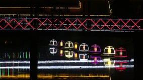 Środka strzał pedestrians widzieć w sylwetce krzyżuje iluminującego footbridge przy nocą w Azja zbiory