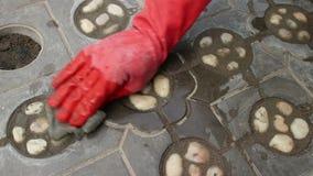 Środka strzał pracownika czerwona gloved ręka gładzi niedawno kłaść kamienie w ti zbiory wideo