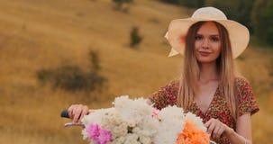 Środkowa plan dziewczyna w sukni iść z rowerem i kwitnie w polu zdjęcie wideo