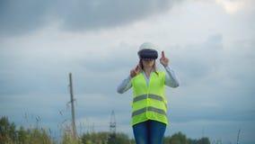Środkowego planu żeński energetyczny inżynier w rzeczywistość wirtualna szkłach i biały hełm na tle wysokonapięciowa władza zdjęcie wideo